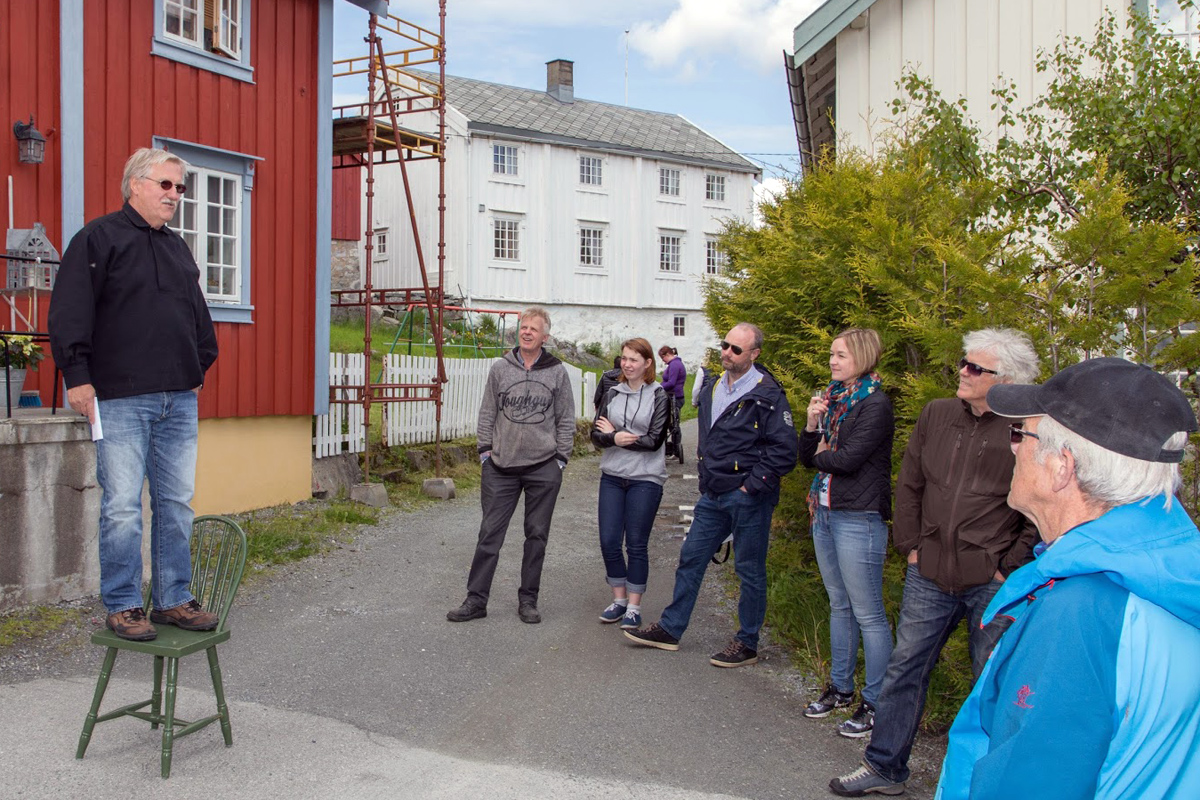 Roar Børø tok med forsamlingen på en historisk vandring ved bryggene der han fortalte noe av historiene bak de ulike bryggene og husene i Råkvågen.